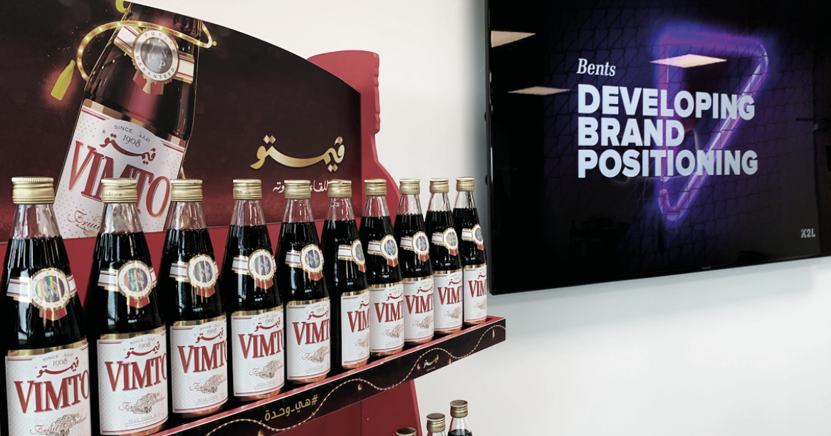 Vimto bottles and the K2L logo on a TV screen